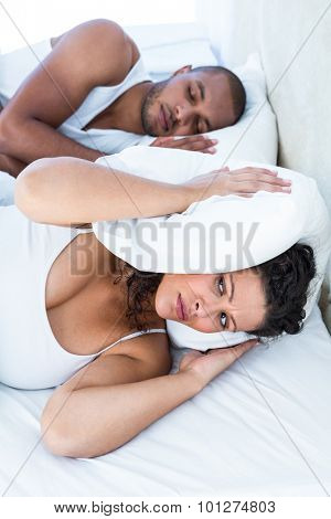 Disturbed wife sleeping besides snoring husband at home