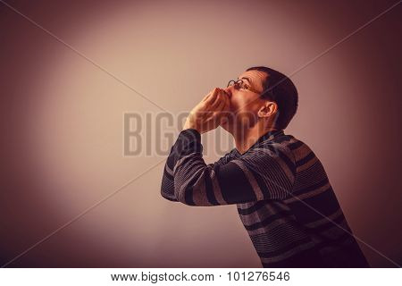 European-looking male put his hands to his mouth, shouting on gr