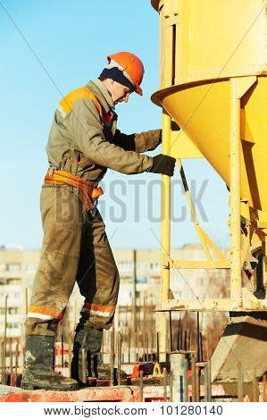 building worker at construction site doing concrete works with barrel