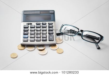 business, finance, money and bookkeeping concept - calculator, eyeglasses and euro coins on office table