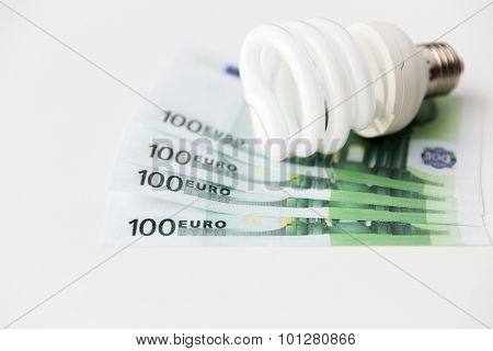 business, finance, energy saving and utilities concept - close up of euro paper money and light bulb on table
