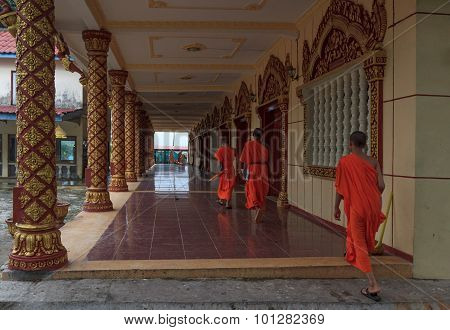 Group Of Young Southeast Asian Buddhist Monks Walk Along Hallway In Wat Krom In Sihonoukville, Cambo