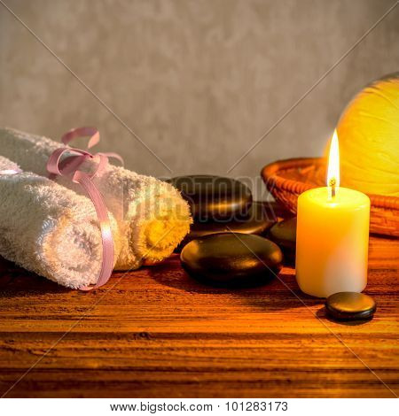Spa Still Life Of White Towels, Candle, Thai Herbal Compress Balls In Basket And Zen Basalt Stones O