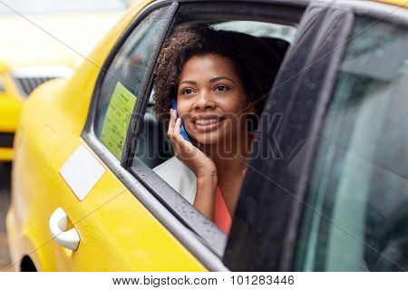 business trip, transportation, travel, gesture and people concept - young smiling african american woman calling on smartphone in taxi at city street