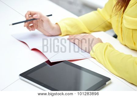 people, technology and education concept - close up of female hands with tablet pc computer writing to notebook at school