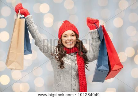 holidays, christmas, sale and people concept - happy young asian woman in winter clothes with shopping bags over lights background
