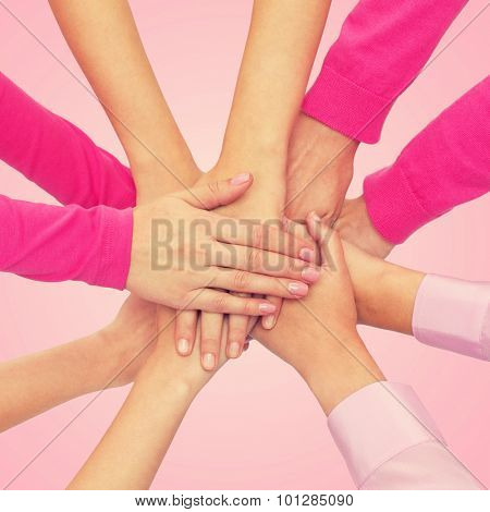feminism, women power and breast cancer awareness concept - close up of women hands on top of each other over white background
