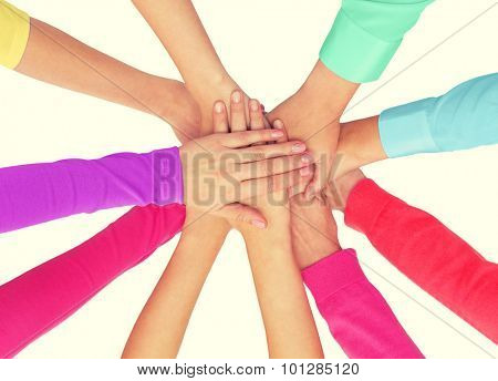 people, gesture, gay pride and homosexual concept - close up of women hands in rainbow clothes on top of each other over white background