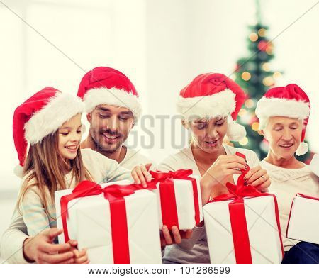 family, happiness, generation, holidays and people concept - happy family in santa helper hats with gift boxes sitting on couch over living room and christmas tree background