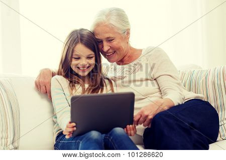 family, generation, technology and people concept - smiling granddaughter and grandmother with tablet pc computer sitting on couch at home