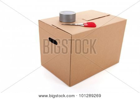 Closed box with scissors and scotch tape isolated over white background