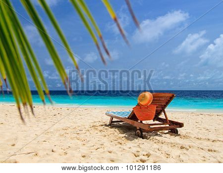 straw hat and bag on a lounge chair at sand beach