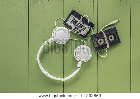 Old Cassette Tape And Head Phone On Green Color Wood Board