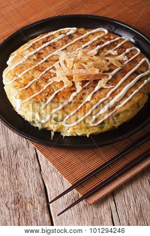 Japanese Okonomiyaki On A Table Close-up And Chopsticks. Vertical