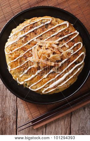 Japanese Okonomiyaki On A Table Close-up. Vertical Top View