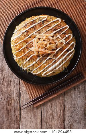 Japanese Okonomiyaki On A Wooden Table. Vertical Top View