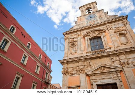 Church With Wall Clock And Old Red House Facade