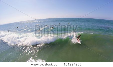 LOS ANGELES - NOV 23, 2014: Woman rides on surfboard at autumn sunny day. Aerial view. The art of surfing was first described in 1769.