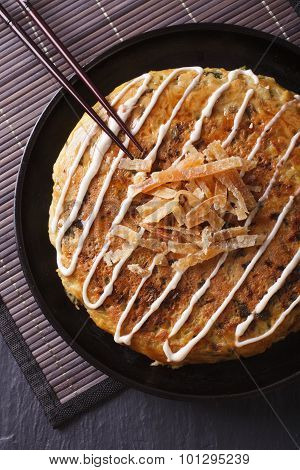 Japanese Food: Okonomiyaki Close-up On A Plate. Vertical Top View