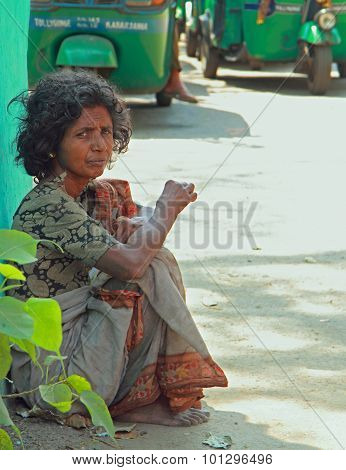 poor woman is sitting on the pavement in Kolkata, India