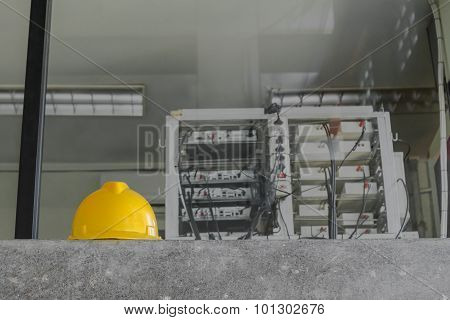 Yellow safety helmet and  Network control room in background