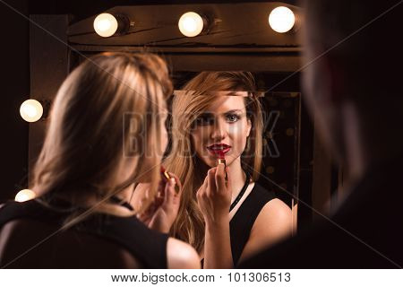 Alluring Woman Applying Red Lipstick