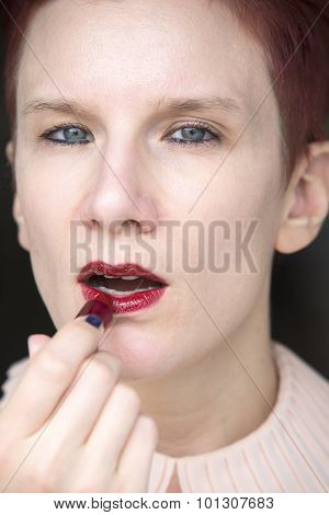 Redhaired Woman Putting Red Lipstick On