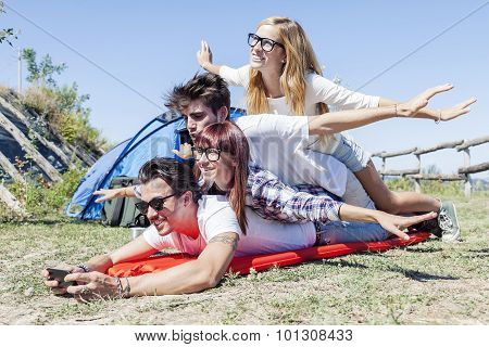 young boys and girls in campsite piled up smiling