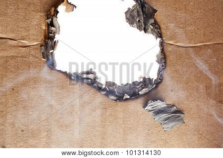 Burnt hole in cardboard