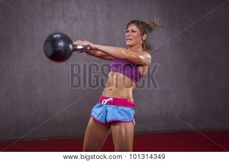 Muscular girl with kettle-bell