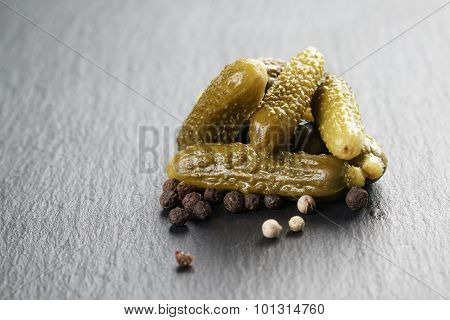 marinated cornichons on slate background