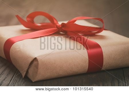 rustic present box with red ribbon on wood table