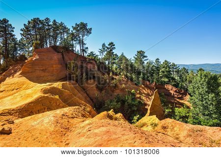 Roussillon, Red village of Provence. Multi-colored outcrops - from yellow to red-orange. Green trees create beautiful contrast from ochre