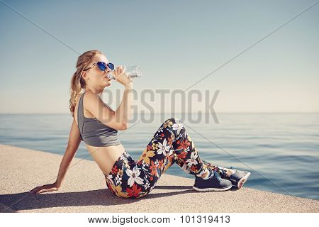 Young Fitness Blonde Woman Drinking Water After Running At Beach. Woman Sport Runner Resting Taking