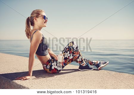 Young Fitness Blonde Woman Hold Bottle Water After Fit At Beach. Woman Sport Runner Resting Taking A
