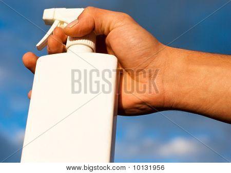Male Hand Holding White Spray Bottle Against Blue Sky Background