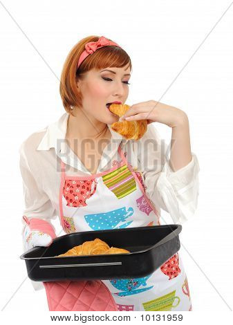 Beautiful Cooking Woman In Apron Eating Fresh Made Croissant Bread. Isolated On White Background