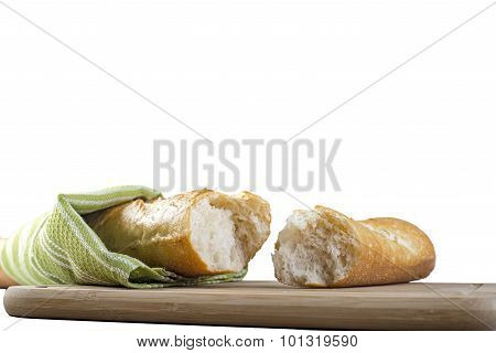 Long baguette broken into pieces on white background