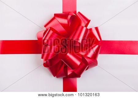 A White Box Tied With A Red Satin Ribbon Bow. A Gift For Christmas.