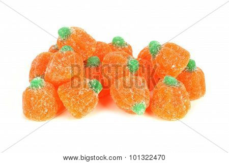 Pile of Halloween gummy pumpkin candies over white