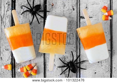 Halloween candy corn popsicles downward view on white wood background