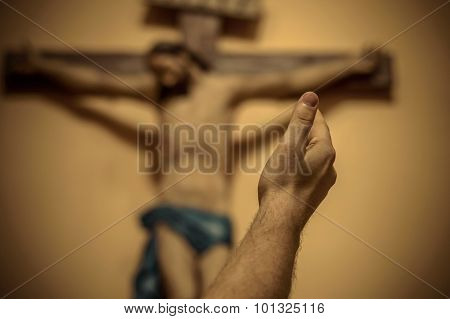 Artitic Vignette Edit Of A Man's Hand Raised Towards Jesus On The Cross