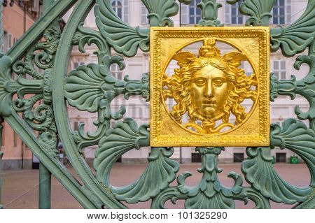 A Golden Face On A Green Gate Castle Fence
