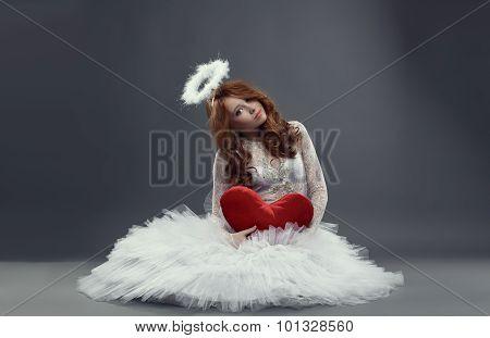 Feminine Cupid. Girl in angel costume with heart