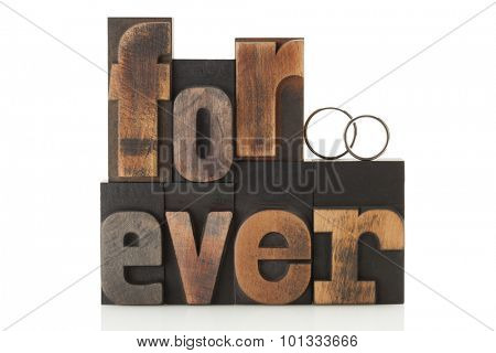 Wedding rings on the word forever, written with vintage letterpress printing blocks