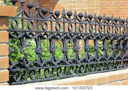 Elegant Wrought Metal Fence Painted With Black Paint Against A Brick Wall