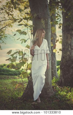 young woman in long white dress lean against big tree looking  away, full body shot, profile, front view,  summer day