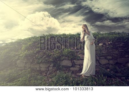 young blonde woman in long white dress with twig of flowers in hand stand by old wall overgrown with grass, outdoor shot, full body shot