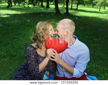 Young loving couple looking at each other and holding a red heart. love story