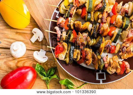 Grilled Skewers On The Plate Made With Chicken, Becon And Vegetables.